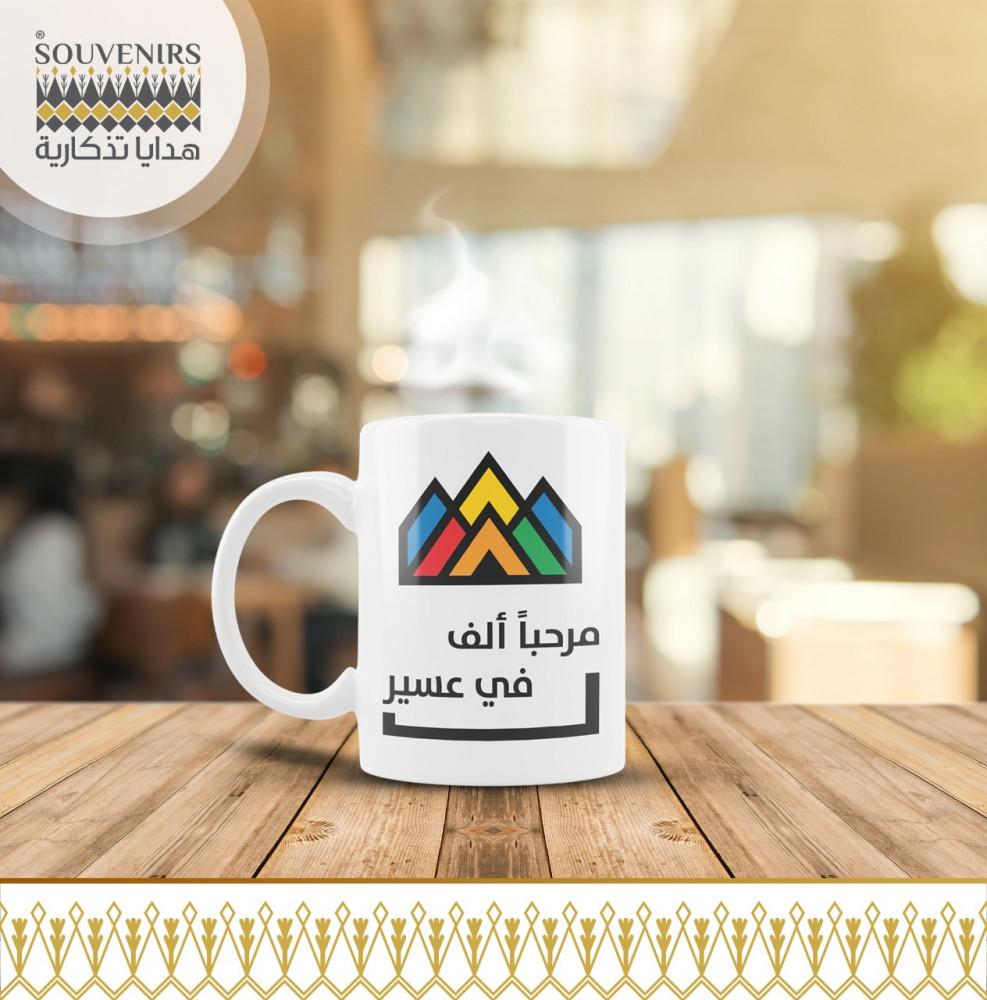 كوب قهوة بشعار مرحبا الف في عسير
