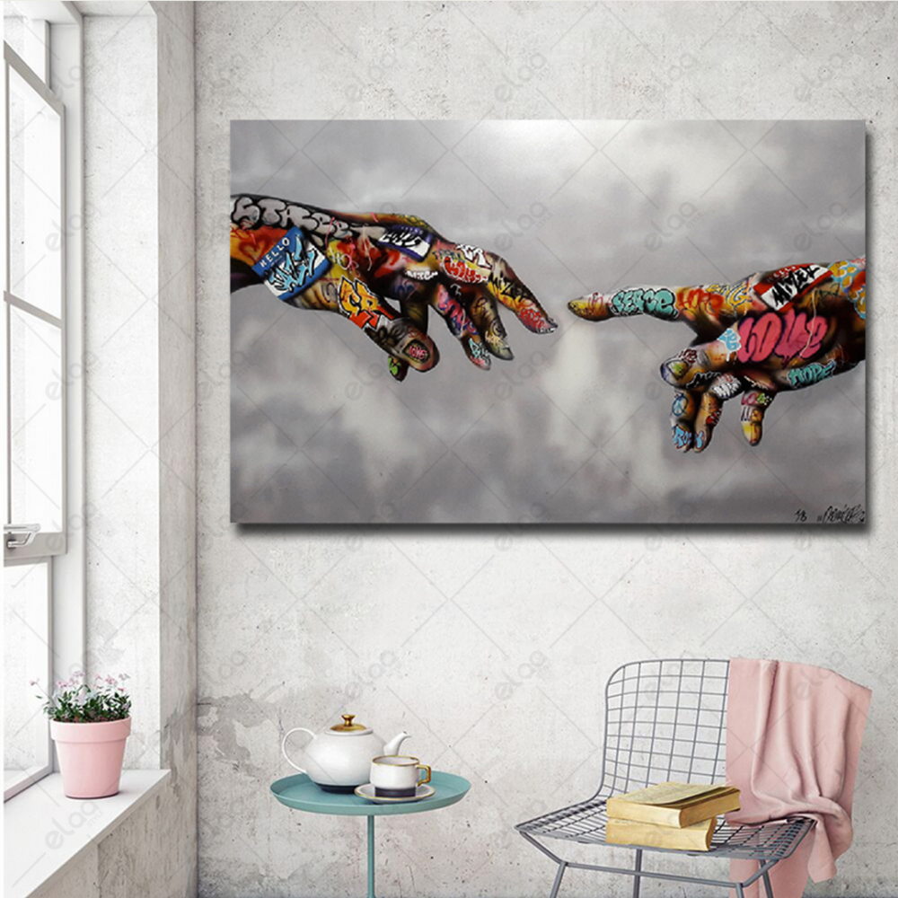 لوحة تشكيلية ليدين معبأة بعبارات الرسم على الجدار